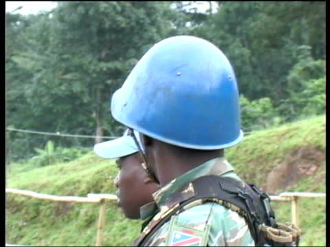 UN security checkpoint Soldier sitting on wall above 'Have A Safe Journey' sign / UN peacekeeper wearing blue helmet standing next to UN soldier...