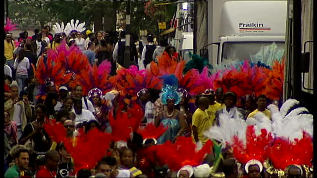 general views of notting hill carnival onlookers taking photographs / group of police officers towards / wide shot of people wearing colouirful... - headdress stock videos and b-roll footage