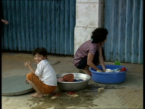 general views of phnom penh; ext children playing on pavement / motorcyclist along / woman and child washing dishes in bowls on pavement / raw sewage... - running shorts stock videos & royalty-free footage