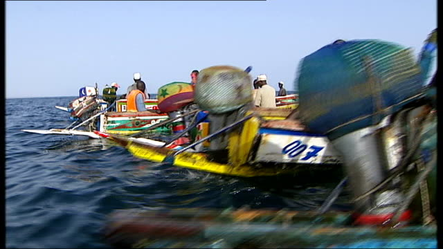 general views of poor fishing community; more of fishermen in boats, showing fish to camera / more of silhouettes of boats in sparkling sea - senegal stock videos & royalty-free footage