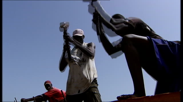 vídeos de stock e filmes b-roll de general views of poor fishing community washing hanging out to dry in the sun / men building boat hammering nails into wood including good silhouette... - senegal