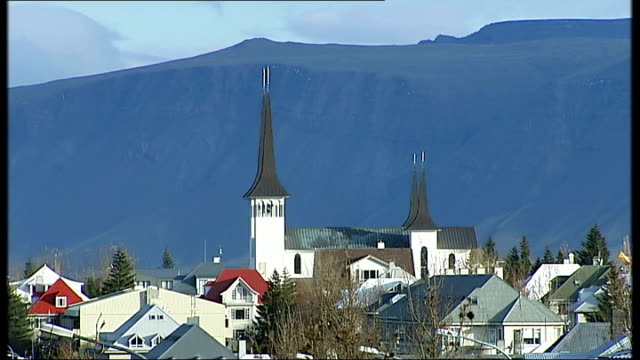 general views of reykjavik general views of seashore sea and cloudcovered mountains / church nestling amid trees and houses mountains in background /... - spire stock videos & royalty-free footage