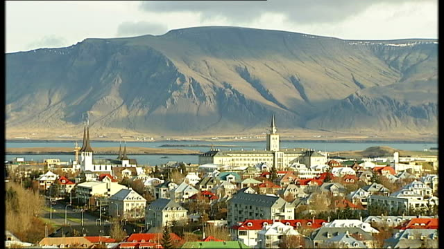 general views of reykjavik snow covered mountains / more of long building with spire / more of cranes and construction sites / various of workers on... - spire stock videos & royalty-free footage