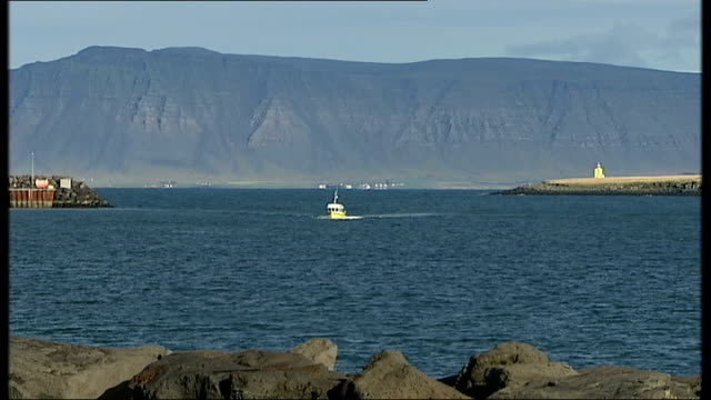 General views of Reykjavik Wide shot of small boat along towards on bay mountains in background / More of boat / Headland with lighthouse on / GVs...