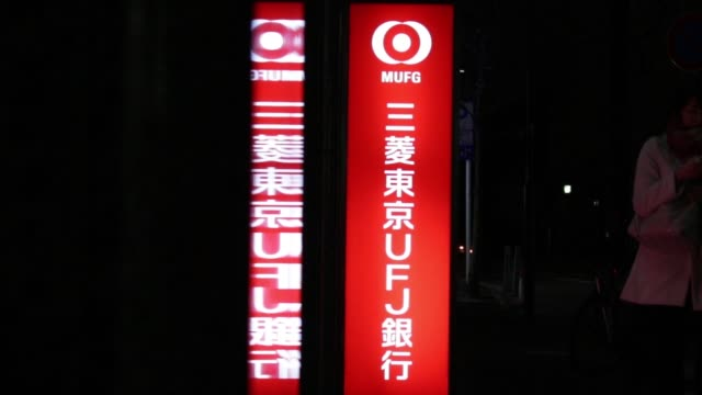 general views of signage and logo of tokyo mitsubishi ufj ltd illuminated at night as pedestrians walk past - general view stock videos & royalty-free footage