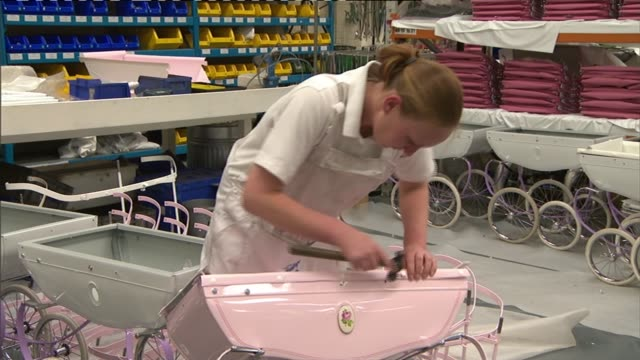 general views of silver cross factory; england: north yorkshire: skipton: silver cross factory: int general views of factory workers assembling pink... - スキップトン点の映像素材/bロール