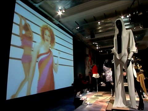 general views of stage costumes on display at kylie minogue exhibition; various of black mannequin wearing white hooded jumpsuit / white hooded... - kylie minogue the exhibition stock videos & royalty-free footage