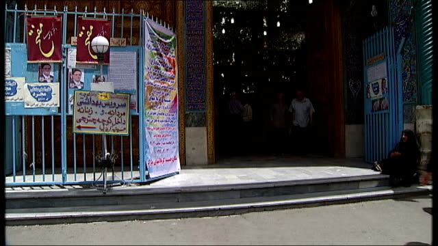 general views of tehran woman handing out leaflets / people holding leaflets and chatting / flags and banners outside mosque / low angle view of... - tinsel stock videos & royalty-free footage