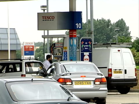 general views of tesco and asda petrol stations england ext motorist filling his car with fuel at tesco petrol station / general view of cars queuing... - tesco点の映像素材/bロール
