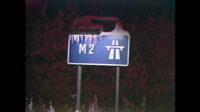 general views of traffic at night in snowfall and a frozen motorway sign in south-east england during arctic blizzards across the uk in january 1987. - major road stock videos & royalty-free footage