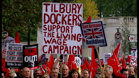 general views of tuc anti-austerity march in london; england: london: ext protester in wheelchair towards / protesters marching along with banner... - 労働組合会議点の映像素材/bロール