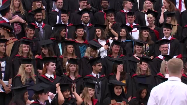 general views of university students at graduation; england: west midlands: warwick: ext students standing on platform and posing for photocall /... - graduation stock videos & royalty-free footage