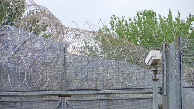 general views of wandsworth prison; england: london: hm prison wandsworth: ext gvs fences, barbed wire and cctv cameras around prison - prison stock videos & royalty-free footage
