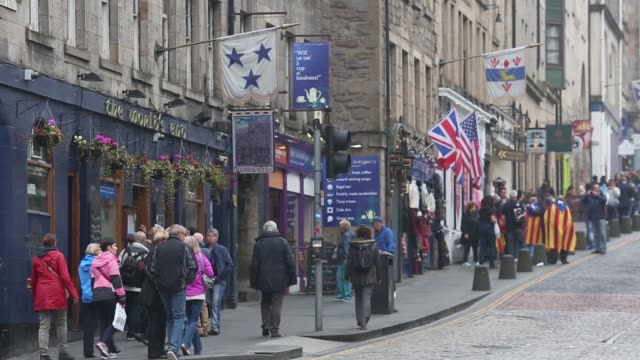 general views pedestrians and vehicles pass along the royal mile on the day of the scottish independence referendum in the old town area of edinburgh... - royal mile stock videos and b-roll footage