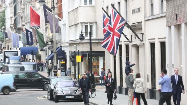 General views pedestrians walking past luxury and designer stores along New Bond Street in London Branded flags hang above luxury goods stores on New...