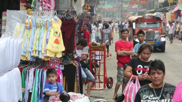 general views shoppers walk past clothes stalls in the market district of divisoria in manila the philippines on monday jan 6 general view... - american eagle outfitters stock videos & royalty-free footage