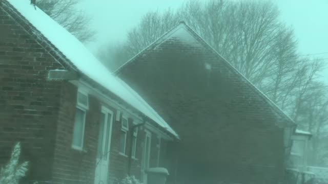 general views snow in the midlands england midlands various of snow covered trees and bushes / snow falling on already snow covered street and some... - slush stock videos and b-roll footage