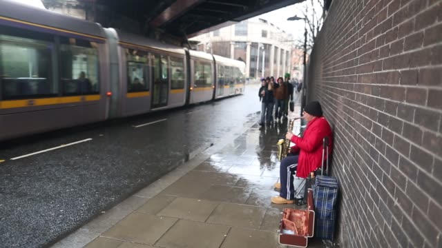 general views street musician/busker playing saxophone people walking past holding umbrellas in the rain dublin street musician on march 17 2013 in... - woodwind instrument stock videos and b-roll footage