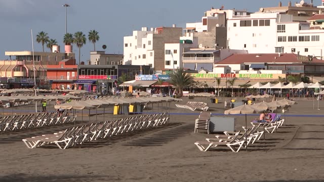 Canary Islands Tenerife Los Cristianos EXT Various of tourists walking along promenade in holiday resort / empty sun loungers on the beach / tourists...