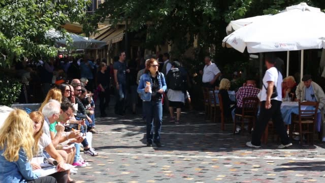 stockvideo's en b-roll-footage met general views tourists and pedestrians walk past café restaurants on ermou street in central athens greece on 29 sept 2014 tourists sit on a wall in... - for sale korte frase