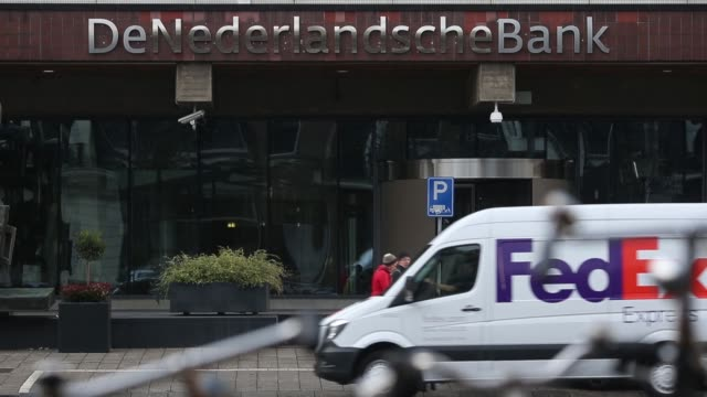 general views traffic and cyclists pass outside the dutch central bank also known as de nederlandsche bank nv in amsterdam netherlands on monday dec... - veicolo terrestre commerciale video stock e b–roll