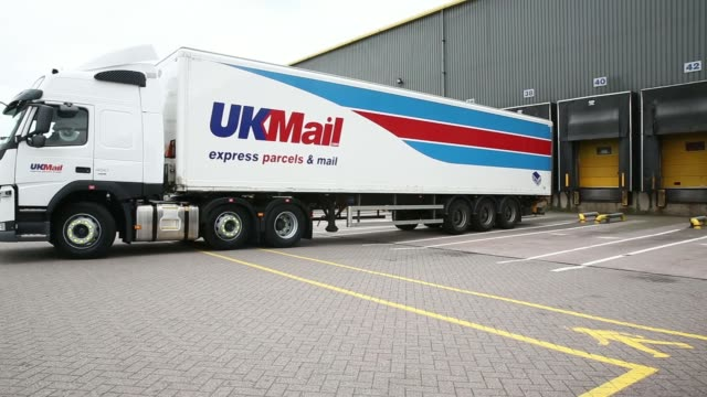 General views UKMail branded delivery trucks and vans stand parked outside loading bays at UK Mail Group Plcs letter and parcel sorting center in...