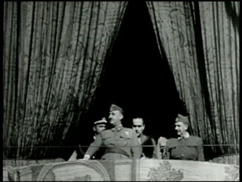 generalissimo francisco franco standing on balcony w/ curtains bg soldiers marching w/ rifles in parade formation . - benito mussolini stock videos & royalty-free footage