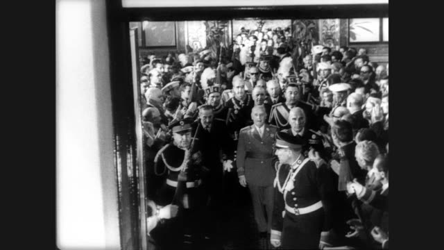 generalissimo francisco franco walks down a street in madrid with his generals as crowd watches and waves flags from the sidewalks / franco shakes... - dictator stock videos & royalty-free footage