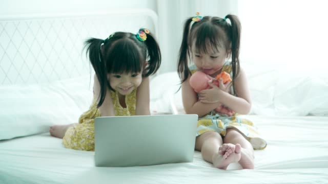 Generation Alpha-Two baby cute girls enjoy playing computer laptop at the bedroom with positive emotion