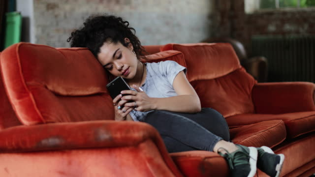 generation z female relaxing on sofa using smartphone - generation z stock videos & royalty-free footage