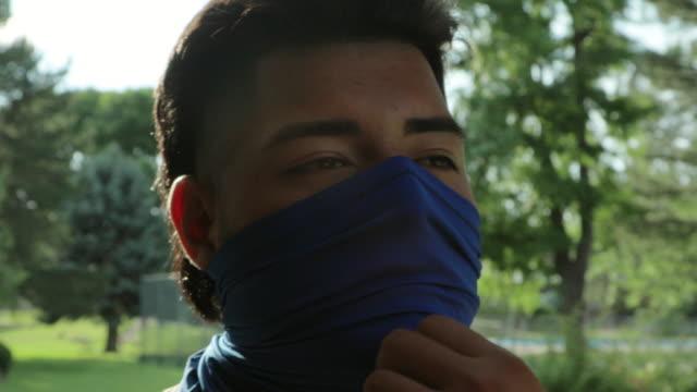 stockvideo's en b-roll-footage met generatie z hispanic atletische man die gezichtsmasker 4k video reeks draagt - generation z