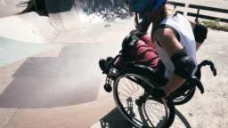 Generation-Z woman in wheelchair in skate park doing stunts - slow motion video