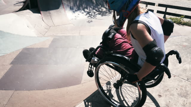 generation-z woman in wheelchair in skate park doing stunts - slow motion video - sports equipment stock videos & royalty-free footage