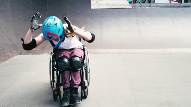 vídeos y material grabado en eventos de stock de generación-z mujer en silla de ruedas en el parque de patinaje haciendo acrobacias - video a cámara lenta - generation z