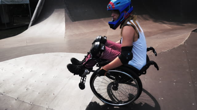 stockvideo's en b-roll-footage met generation-z vrouw in rolstoel in skatepark stunts doen-slow motion video - behendigheid