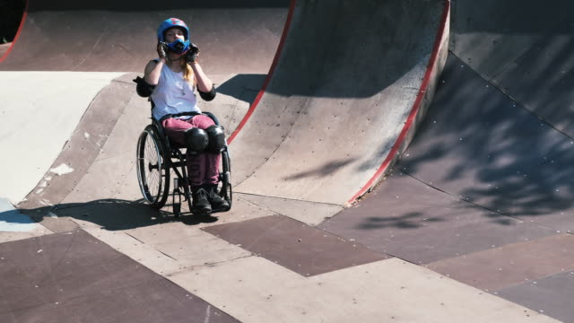 generation-z frau im rollstuhl im skatepark macht stunts - slow-motion-video - mut stock-videos und b-roll-filmmaterial