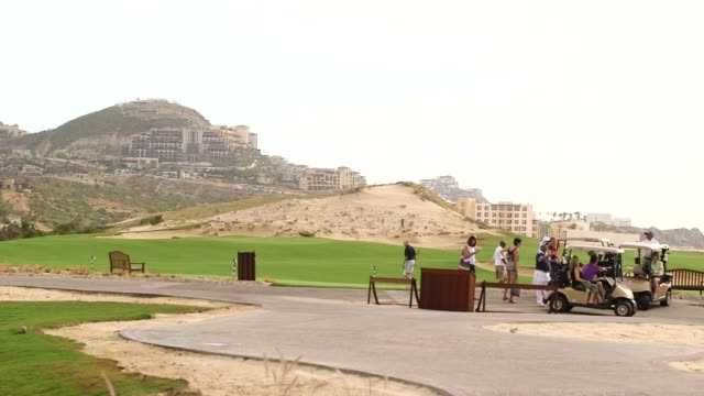 vidéos et rushes de generic broll of golfers playing golf and driving around palmilla golf course on golf carts in los cabos mexico close up shots and wide shots of... - tee de golf