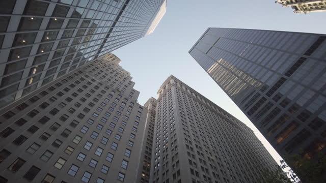 vidéos et rushes de generic manhattan new york city skyscraper views with multiple high-rise buildings filmed directly from below with subtle rotational camera movement. - vue en contre plongée