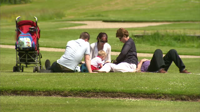generic people walking around park during british summertime ,sunny weather, includes elderly oap man on bench and family sunbathing on green people... - picnic stock videos & royalty-free footage
