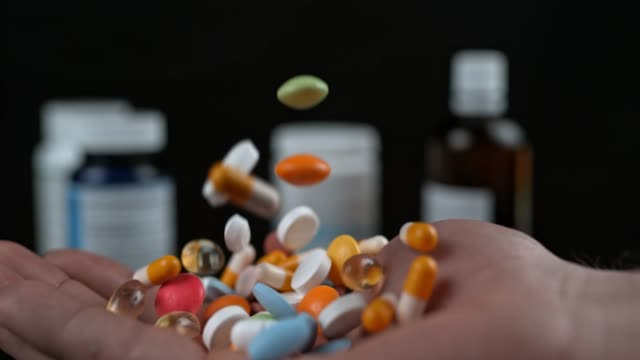 slo mo generic pills falling on an open palm - pill addiction stock videos & royalty-free footage