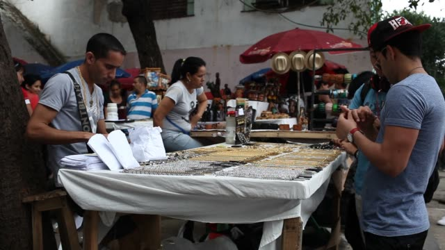 generic shots of customers browsing goods at various outdoor street vendors in havana, cuba, a street vendor selling jewelry speaks with customers as... - latin america stock videos & royalty-free footage