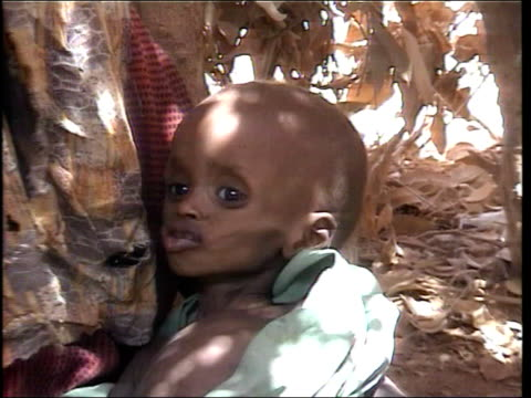 stockvideo's en b-roll-footage met ethiopia genetically modified aid ethiopia woman holding starving child cargo ship in harbour boxes of aid from the usa being unloaded boxes along on... - hongerig