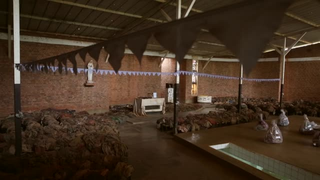 ws genocide victims' bloodstained clothing possessions and bones are on display inside the nyamata catholic church memorial ahead of the 20th... - völkermord stock-videos und b-roll-filmmaterial
