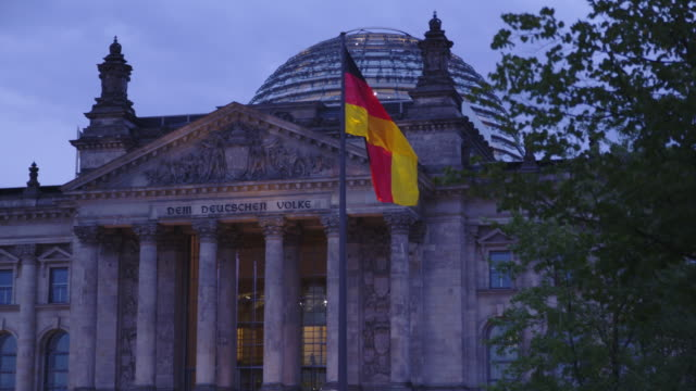a gentle breeze blows through a german flag in front of the reichstag. - german flag stock videos & royalty-free footage