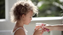 Gentle footage of cute little girl with sunshine in hair drink water from glass