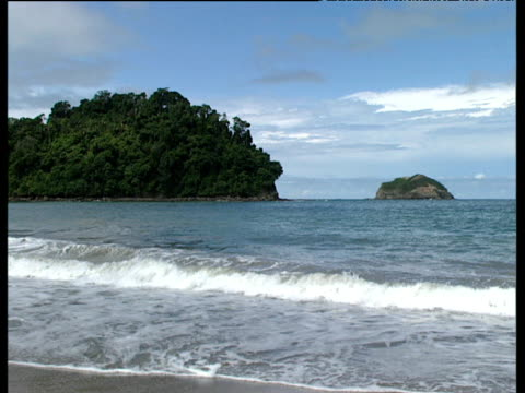 Gentle waves come in to shore tree covered headland in the background. Quepos Costa Rica