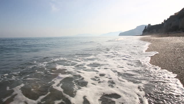 gentle waves lap against sand and pebble beach, sunrise - pebble stock videos & royalty-free footage