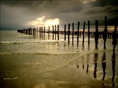 Gentle waves lap onto empty beach with wooden pillars as sun sets under grey clouds England