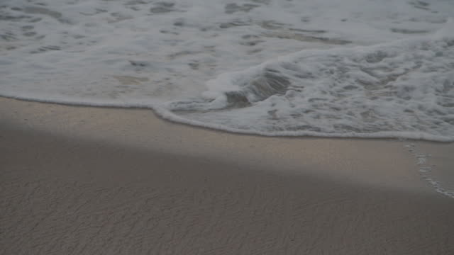 gentle waves lap over smooth sand at dusk - water's edge stock videos & royalty-free footage