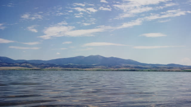 gentle waves on lake de smet in wyoming with the rocky mountains in the background on a sunny day - lakeshore stock videos & royalty-free footage
